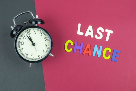 Top view of last chance wording and classic vintage alarm clock on colorful red and black background Stok Fotoğraf