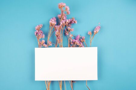 Cute dried violet statice flower with white paper card on top on blue background in vintage tone