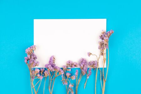 Top view of cute dried violet statice flower with white paper card on blue background in vintage tone
