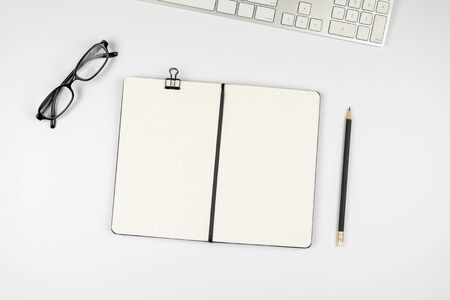 Table top view of office desk with empty grid notebook with black pencil on white background