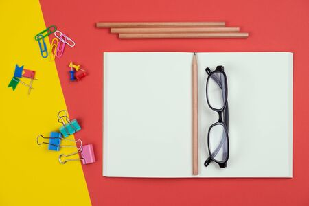 Top view of an empty blank open notebook with pencil and stationery items and eyeglasses on the colorful background