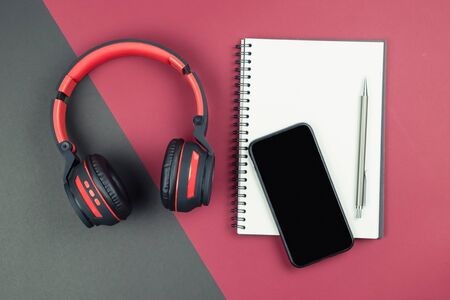 Top view of empty blank notebook with pen smartphone and headphone on red black background Stok Fotoğraf