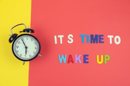 Top view of It's time to wake up wording with classic vintage alarm clock on colorful red and yellow background Stok Fotoğraf