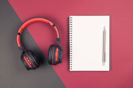 Top view of empty blank notebook with pen and headphone on red black background in vintage tone