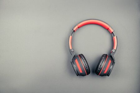 Top view of black and red headphone on black background in vintage tone