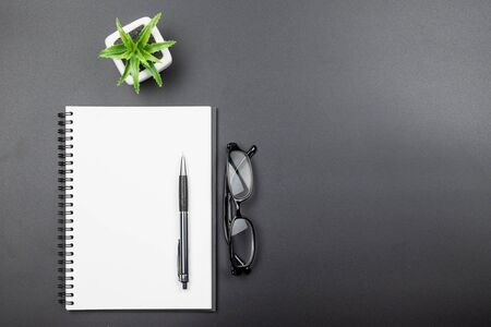 Table top view of empty blank page notebook with pen and eyeglasses on black background