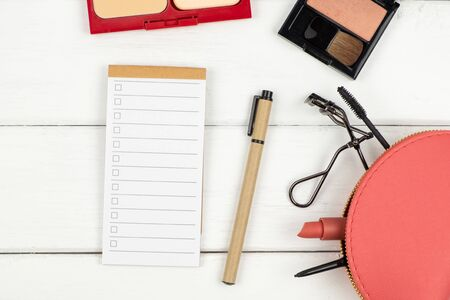 Top view of cosmetic items notebook and pen on white wood background