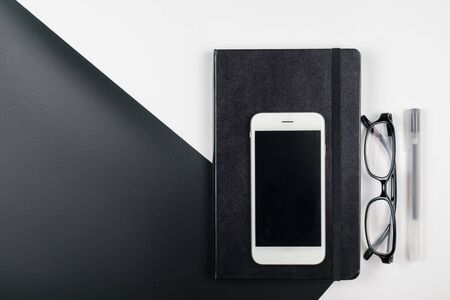 Top view of minimal office desk with notebook pen mobile phone and eyeglasses Stok Fotoğraf