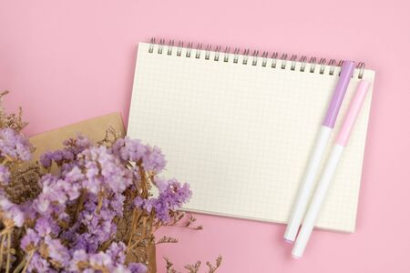 Top view of empty grid notebook and violet statice and white caspia flower bouquet on pastel pink background