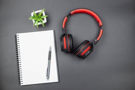 Table top view of empty blank page notebook with pen and headphone on black background