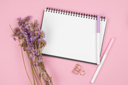 Top view of blank empty notebook with pens and paper clip and violet statice flower bouquet on pastel pink background