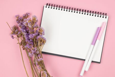 Top view of blank empty notebook with pens and violet statice flower bouquet on pastel pink background