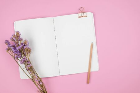 Top view of dot grid notebook with pencil, paper clip and violet statice flower bouquet on pastel pink background Stok Fotoğraf