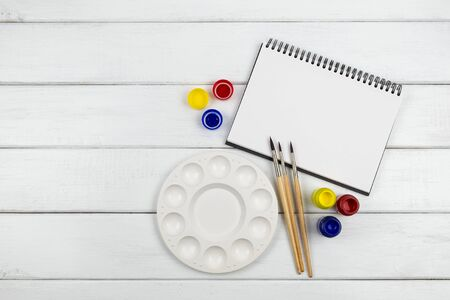 Top view of a blank art book with water color and paintbrush on white wooden background Stok Fotoğraf