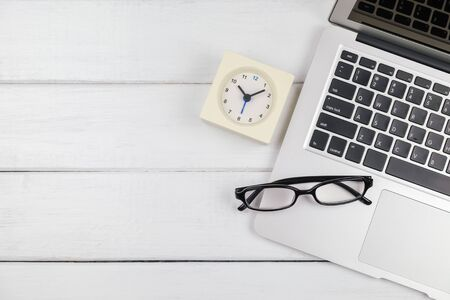 Table top view of laptop and white clock with empty space on white wooden background