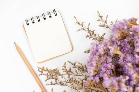 Top view of a blank paper note with pencil and a cute caspia and statice flower bouquet on white background Stok Fotoğraf