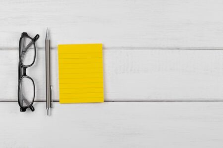 Top view of a yellow blank sticky note with pencil and eyeglasses on white wooden background