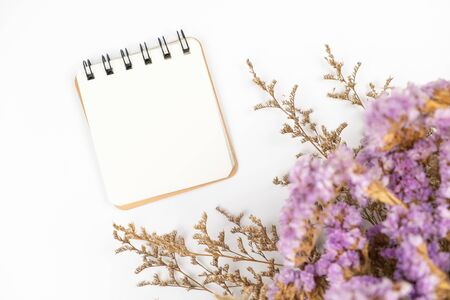 Top view of a blank paper note with a cute caspia and statice flower bouquet on white background