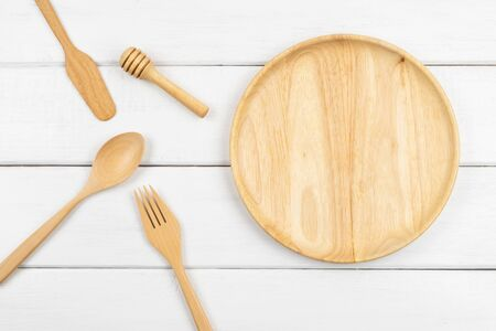 Top view of a wooden dish with spoon, fork, butter knife, and honey dipper on white wooden background