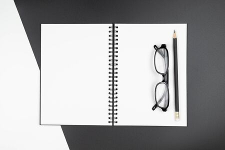 Top view of an empty open notebook with black pencil and eyeglasses on black and white background