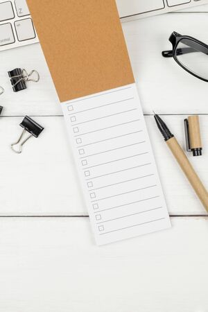 Top view of To Do List paper with a brown pen and stationery items on white wood minimal office desk Stok Fotoğraf - 131474905