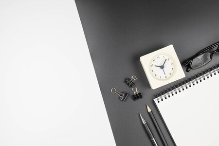 Top view of an open notebook with stationery items and clock on black and white background Stok Fotoğraf