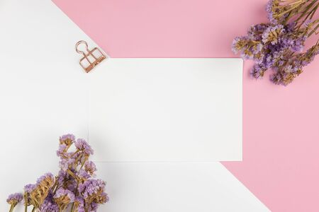 Top view of a blank paper note with paper clip and purple statice flower bouquet on pastel pink and white background Stok Fotoğraf