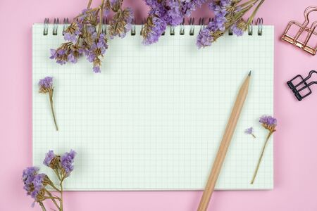 Top view of blank grid notebook with a brown pencil and purple caspia flower bouquet on pastel pink background Stok Fotoğraf