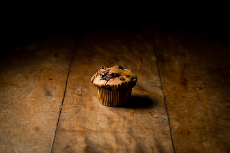 chocolate chip muffin or cupcake on wood table, side lighting, product photography. close up, dark shadows