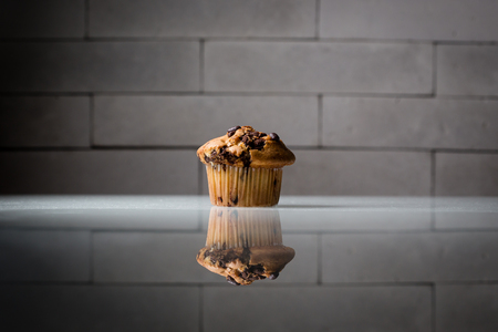 chocolate chip muffin or cupcake on glass table, grey brick background, side lighting, product photography, hard shadows Stock fotó