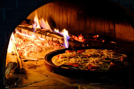 Horno de ladrillo con pizza casera caliente cocinando dentro