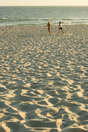 silhouette of two friends (boys) running along the beach during 新聞圖片