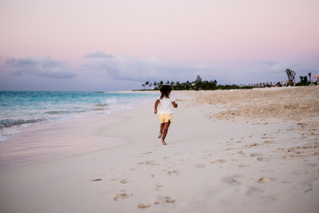 girl running on beautiful beach with turquoise water in Grace Bay during sunset, fully clothed, Providenciales, Turks and Caicos.