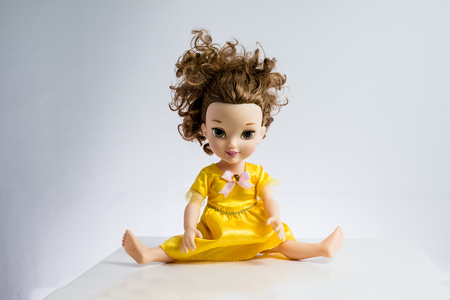 used pretty doll with messed up hair in pretty dress again white backdrop, legs wide open Фото со стока