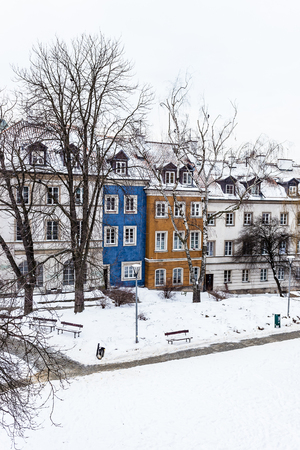 colored houses in warsaw old town after snow storm in winter, colorful exteriors against the white snow.