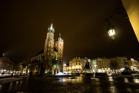 St. Marys Basilica at night, with night lamp visible and dramatic lights, Krakow, Poland.