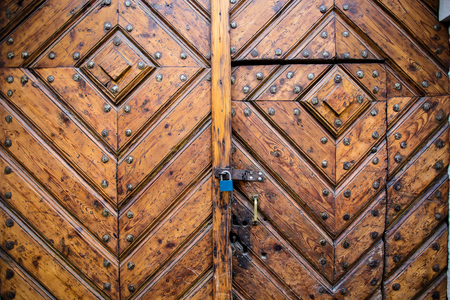 detail of old wooden door with metal lock and padlock, Krakow, Poland.