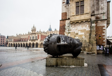 Krakow, Poland - January, 2014: Head sculpture Eros Bendato on Market Square by artist Igor Mitoraj with Sukiennice cloth hall behind