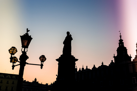 Silhouette of statue and townhall in Market Square during beautiful coloured sunset, Krakow, Poland.