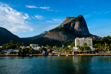 View of the Gavea Stone, seen from below with houses on the hill during late afternoon. Barra da Tijuca, Rio de Janeiro. Banque d'images