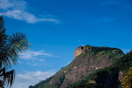 View of the Gavea Stone, seen from the street with houses on the hill during late afternoon. Barra da Tijuca, Rio de Janeiro. Banque d'images