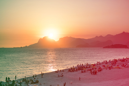 Orange sunset by the ocean in Piratininga, Niteri, with sun dipping behing the Gavea Stone in Rio de Janeiro. A beach full of people can be seen in the foreground in shadow.