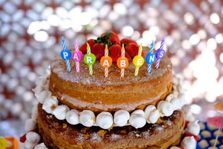 detail of strawberry and meringue naked cake, seen from above, 3 stories high. Translation of candles mean congratulations