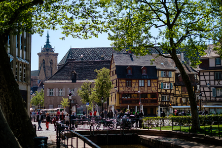 Gorgeous cobbled street in Colmar, Alsace, with people walking around during spring. Stock Photo