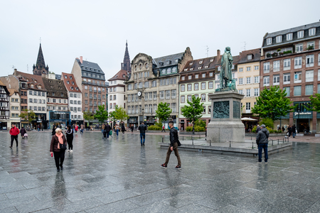 Strasbourg, France - April 27, 2017 : People walking in Place Kleber on a rainy day, with the ornate buildings and statues in the background.