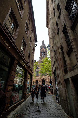 Strasbourg, France - April 27, 2017 : People walking through an alley on a rainy day, with the church tower in the background.