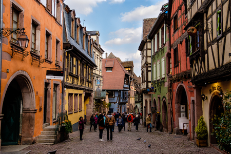 Riquewihr, France - April 27, 2017 : People walking in street with half-timbered houses on a sunny day, with the ornate buildings and statues in the background.