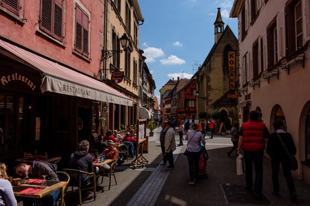 Ribeauville, France - April 27, 2017 : People walking in street with half-timbered houses on a sunny day, with the ornate buildings and statues in the background.