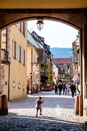 Riquewihr, France - April 27, 2017 : Girl running walking in street with half-timbered houses on a sunny day, with the ornate buildings and statues in the background. 新聞圖片