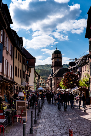 Kaysersberg, France - April 27, 2017 : People walking in street with half-timbered houses on a sunny day, with the ornate buildings and statues in the background. 新聞圖片